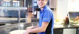 Ein Mitarbeiter von Dominos Pizza Schweiz rollt einen Pizzaboden aus