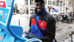 Ein Driver von Dominos Pizza Schweiz liefert eine Bestellung aus