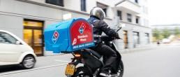Ein Driver von Dominos fährt auf einem Roller eine Pizzabestellung zu einem Kunden