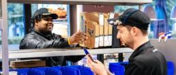 Ein Driver von Dominos Pizza Schweiz bereitete eine Lieferung vor während der Store Manager die Bestellung bearbeitet