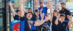 Mitarbeiter von Dominos Pizza Schweiz posieren lächelnd und jubelnd für ein Foto vor einer Filiale