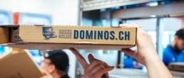 Ein Mitarbeiter von Dominos Pizza Schweiz halt einen Pizzakarton in die Kamera