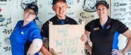3 Mitarbeiter von Dominos Pizza Schweiz lächeln in die Kamera. Einer hält ein Schild in der Hand mit der Aufschrift We want you